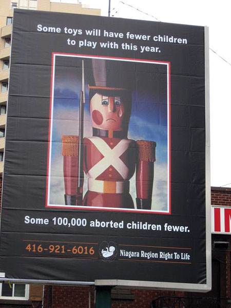 A single tear runs down the face of a wooden toy soldier. The copy reads: Some toys will have fewer children to play with this year. Some 100, 000 aborted children fewer.