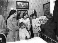 Family reads Armistice Day headlines, November 11, 1918. Pictured left to right: Mrs. J. Fraser, Jos. Fraser Jr., Miss Ethel James, Frank James, and Norman James. City of Toronto Archives, Fonds 1244, Item 892.
