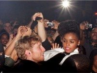 Janelle Monáe goes crowd surfing at the 2011 Indie Awards, while audience members snap pictures and a creepy man wears a black mask