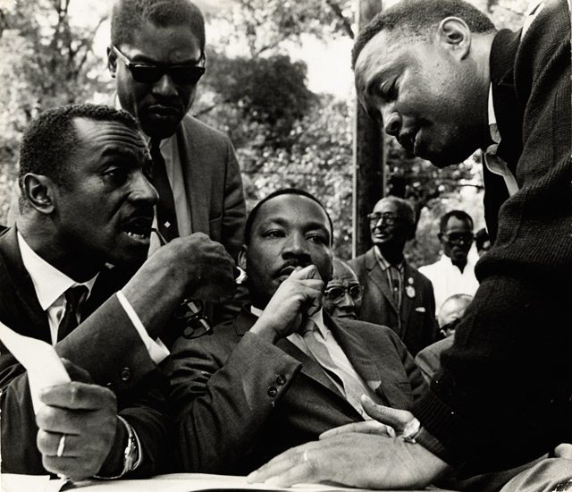 Martin Luther King sitting with group of people standing around him