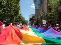 Marchers carry a giant rainbow flag during the 2012 Toronto Pride Parade.