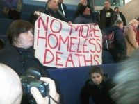 Protestors at City Council unfurl a banner before being removed from council proceedings on shelter access. Photo by Desmond Cole