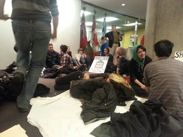 Protesters sit outside Mayor Rob Ford's office to demand better shelter access. Photo by Sarah Roebuck.