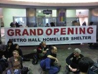 Protestors concerned about shelter access gather in the Metro Hall rotunda.