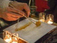 Ninutik's Richard Brault ladles boiling maple syrup onto a bed of snow and carefully wraps a piece of cheese.