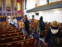 Cyclists line up to have their rides blessed by Reverends Vicki Obedkoff and Hans van Nie.