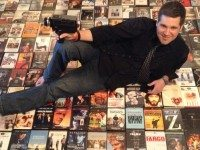 Jason Denis splayed on a bed of movies. Photo by Nikita Rowe.