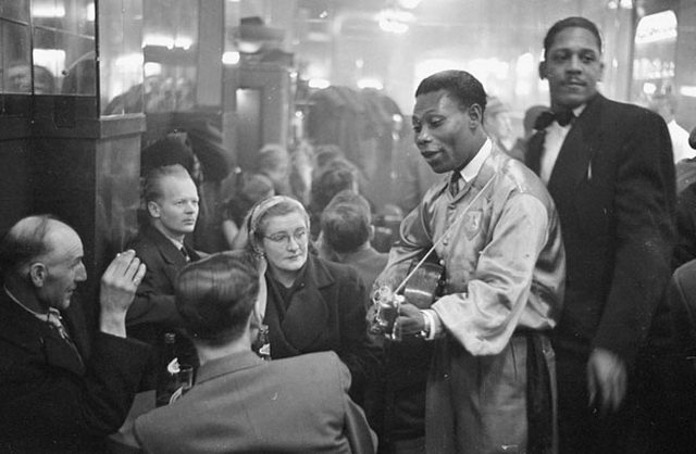 Calypso singer Lord Caresser visits diners at the Rockhead's nightclub in Montreal, April 28, 1951  Photo by Louis Jaques in Weekend Magazine from the Library and Archives Canada