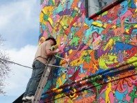 A screenshot of Al Runt working on the mural at Electric Mud BBQ in Augusto Monk's new documentary, RUNT.
