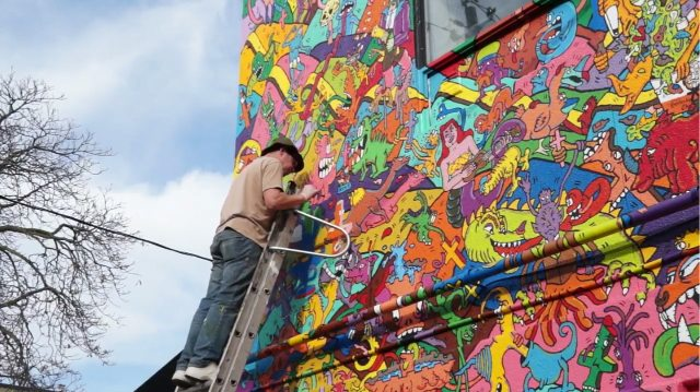 A screenshot of Al Runt working on the mural at Electric Mud BBQ in Augusto Monk's new documentary, RUNT