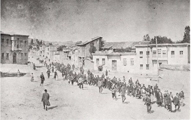 Armenians are marched to a nearby prison in Mezireh by armed Turkish soldiers, 1915. Photo originally published by the American Red Cross. Licensed under Public Domain via Wikimedia Commons