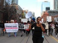 A member of Black Lives Matter Toronto chants into a megaphone as fellow protesters follow her lead.
