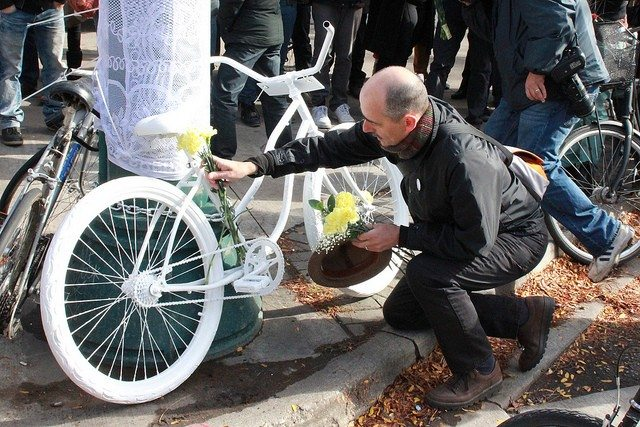 Martin Reis places flowers on the ghost bike for Carla Maria Warrilow  Photo by Warren McPherson, from the Torontoist Flickr Pool