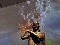 Bronze of a woman fastening her peplos, positioned in front of an animated display of Mount Vesuvius erupting.