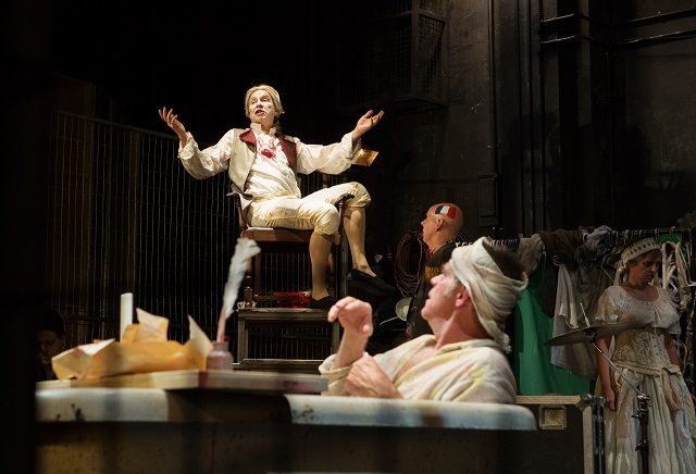 The Marquis de Sade (Diego Matamoros, in chair) expounds his philosophy while Marat (Stuart Hughes, in bathtub) listens, in a scene from Marat/Sade  Photo by Cylla von Tiedemann