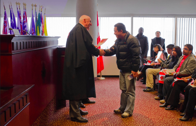 A new Canadian swears the oath of citizenship  Photo by asianz from the Torontoist Flickr Pool