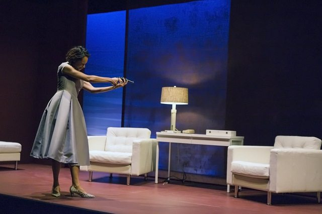 Cara Ricketts as Hedda plays with one of her father's pistols in a scene from Hedda Gabler  Photo by Michel Mersereau