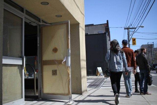 People take a quick glance inside the site of former Starbucks on 1092 Queen Street West, where it remains an empty space during construction.