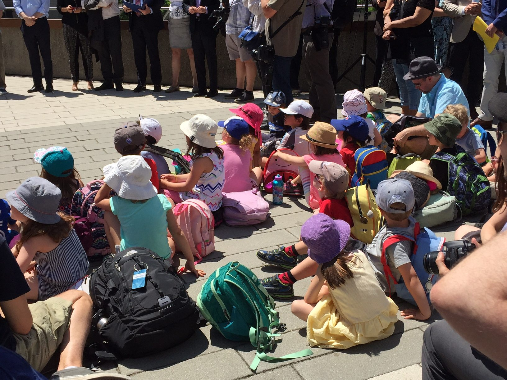 A group of kindergarteners from Clinton Public School watch speeches from the rooftop podium. Their teacher, Mr. V, brings his class every year to the flag raising.