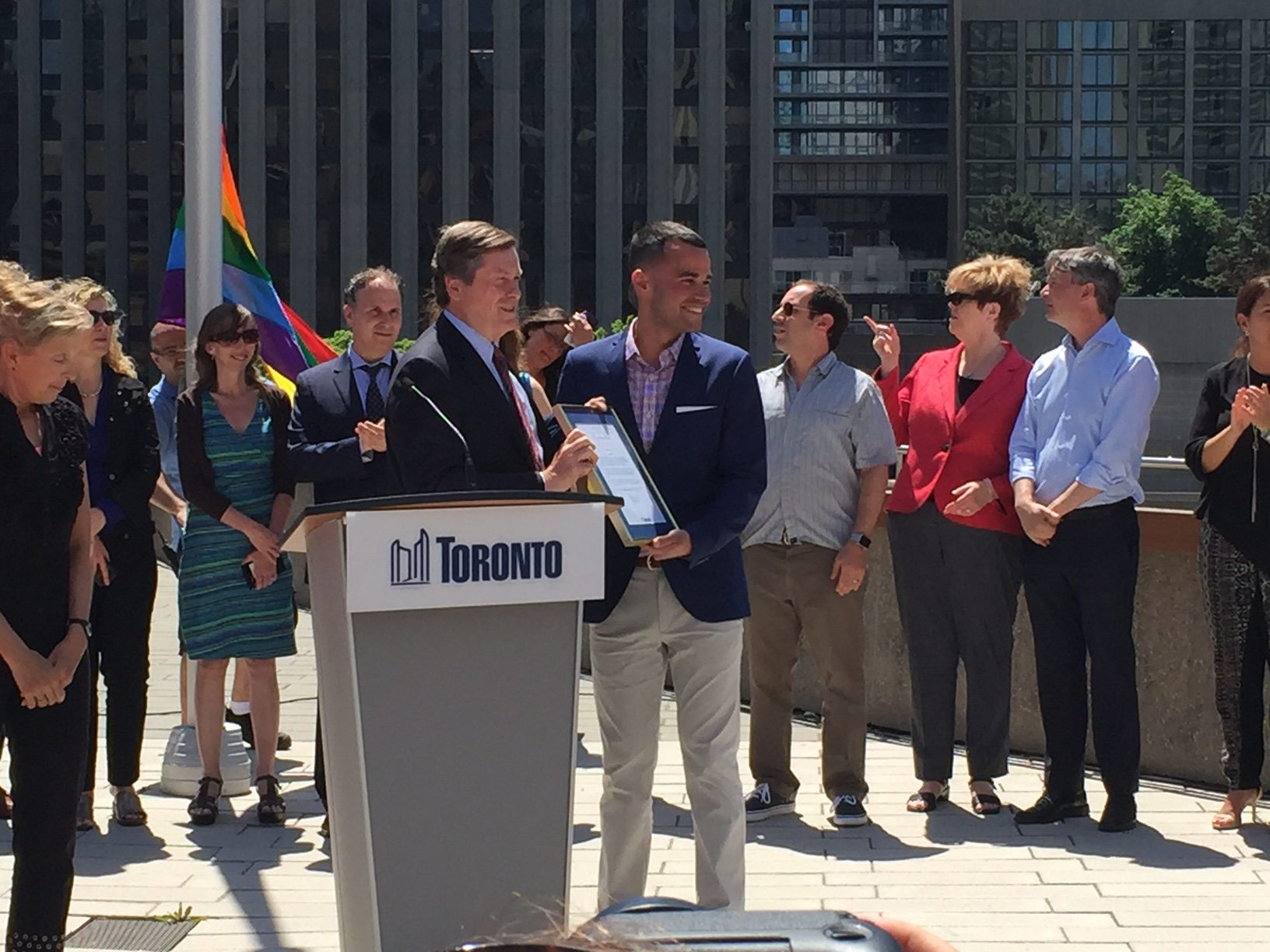 Pride Toronto's Aaron GlynWilliams and Mayor John Tory pose with the City's proclamation of Pride Month.