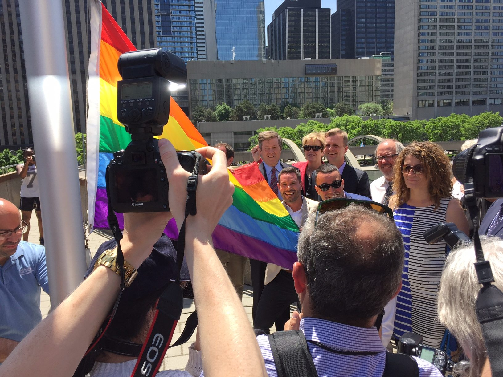 Reporters gather to snap photos as the rainbow flag is raised.