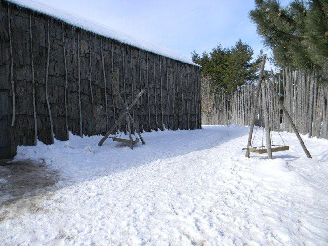 A reconstructed Iroquoian longhouse and palisade at Iroquoian Village near Burlington. Photo from Wikimedia Commons.