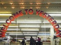 "Walking up the stairs, the well-known ""Welcome to Yesterday"" sign greets customers to a retro-style department store, seen on the mirror at Honest Ed's east side store in Toronto on March 12, 2016."