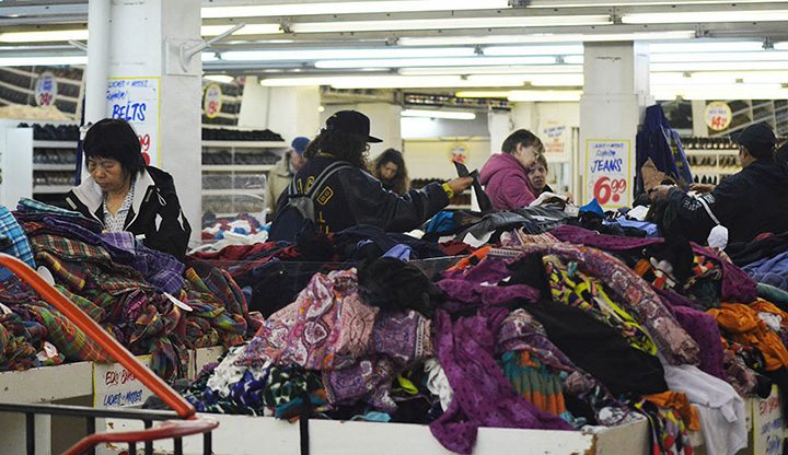 People young and old shop in the messy pile of clothes on sale on the second floor of Honest Ed's east side store in Toronto on March 12, 2016.