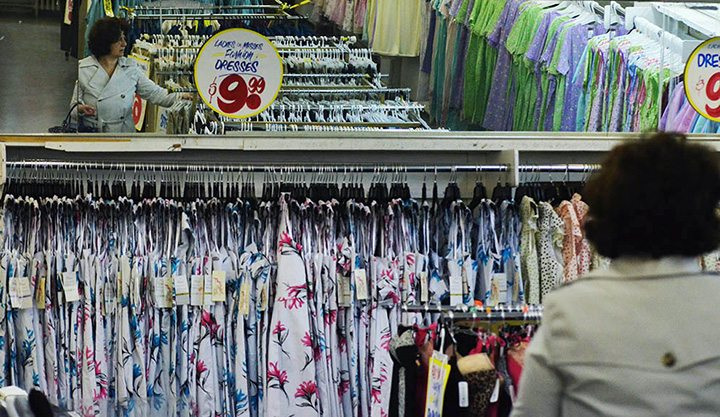 A woman shopping is reflected in the mirror above a dress section somewhere in Honest Ed's east side store in Toronto on March 12, 2016.