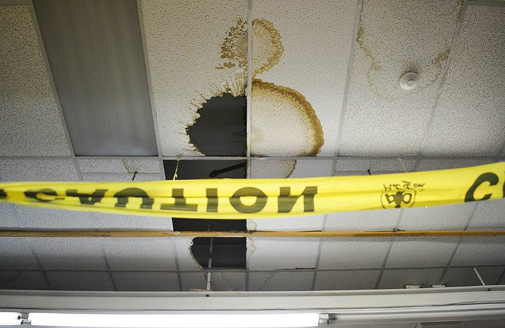 Caution tape is placed below a gigantic hole in the celling that's leaking on clothes somewhere in Honest Ed's east side store in Toronto on March 12, 2016.