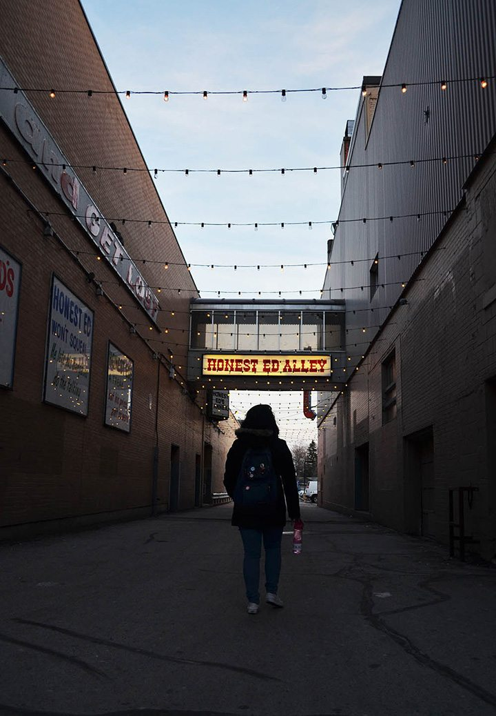 While the sun sets for the evening, Isabelle Docto walks through the well-known Honest Ed's alley that connects the west side and east side stores together in Toronto on March 27, 2016.
