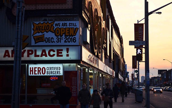 As the sun sets, a sign remains alongside Honest Ed's gigantic logo, telling customers that the store is still open until Dec. 31, 2016, as it anticipates to close down permenantly by the end of the year at Bathurst Street in Toronto on March 27, 2016.