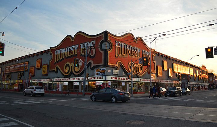 The signs of Honest Ed's begins to light up as the sun starts to set for the evening at the intersection of Bloor Street and Bathurst Street in Toronto on March 27, 2016.