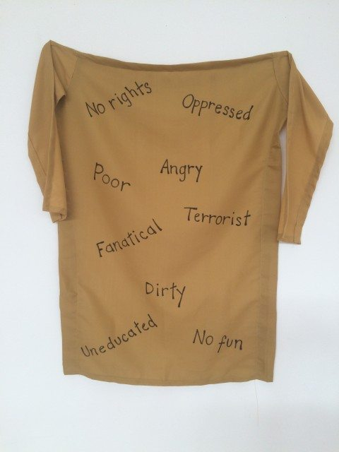 A traditional Kameez silkscreened with words used to describe Muslim women on display at Gardiner Museum's special exhibition hall, photo by Samira Mohyeddin