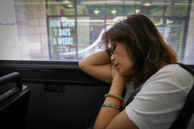 About an hour into her commute, Baylon closes her eyes on a bus from St. Clair Station.