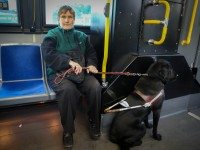 Debbie Gillespie rides the bus with her guide dog, Leroy.