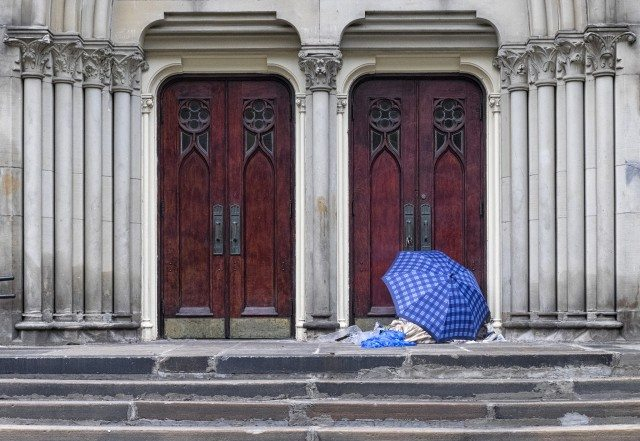 Someone takes shelter at Metropolitan United Church on Queen St. E.
