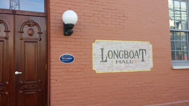 A blue legacy plaque for Tom Longboat installed on a wall. Photo courtesy of Camille Bégin and Heritage Toronto.