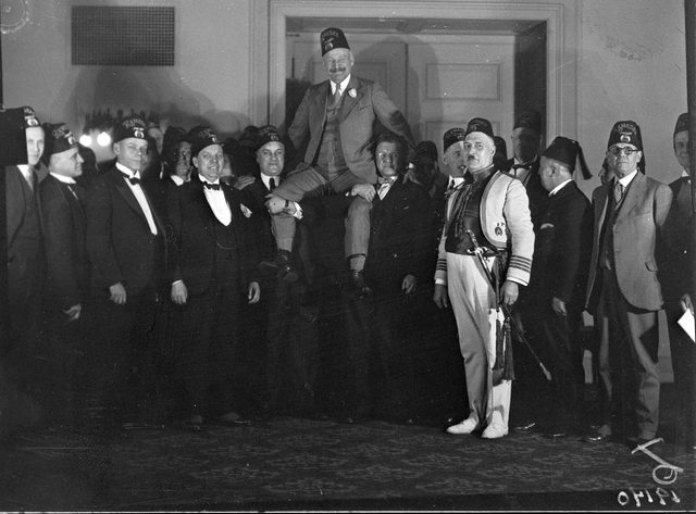 """Police Chief Dennis Draper, shown here """"being chaired by Nobles"""" at the """"Ramses Tample.""""  City of Toronto Archives, Fonds 1266, Item 19140."""