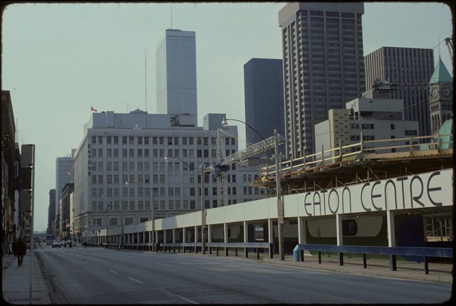 View of exterior of Eaton Centre construction site, with sign. The Queen Street Eaton's store can be seen in the background. Photo by Harvey R. Naylor, April 18, 1975. City of Toronto Archives, Fonds 1526, File 84, Item 60.