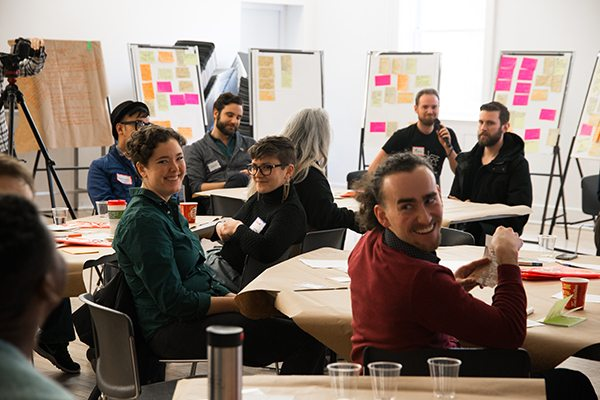 Attendees of the No More S#%&! event laugh during the World Cafe and discussion part of the afternoon. Sticky notes on the boards describe issues and possible solutions for community relations with the police. Photo by Justin Morris and used courtesy of Myseum of Toronto.