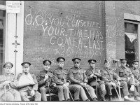 "War wounded in 1916 sit under graffiti, possibly at Yonge and Carlton, including ""don't forget us."" From the City of Toronto Archives Fonds 1244, Item 736."