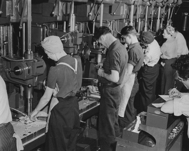Men and women turning out parts for bomber planes at Ford's Willow Run plant, ca. July 1942. From the U.S. National Archives and Records Administration via WikiMedia Commons.