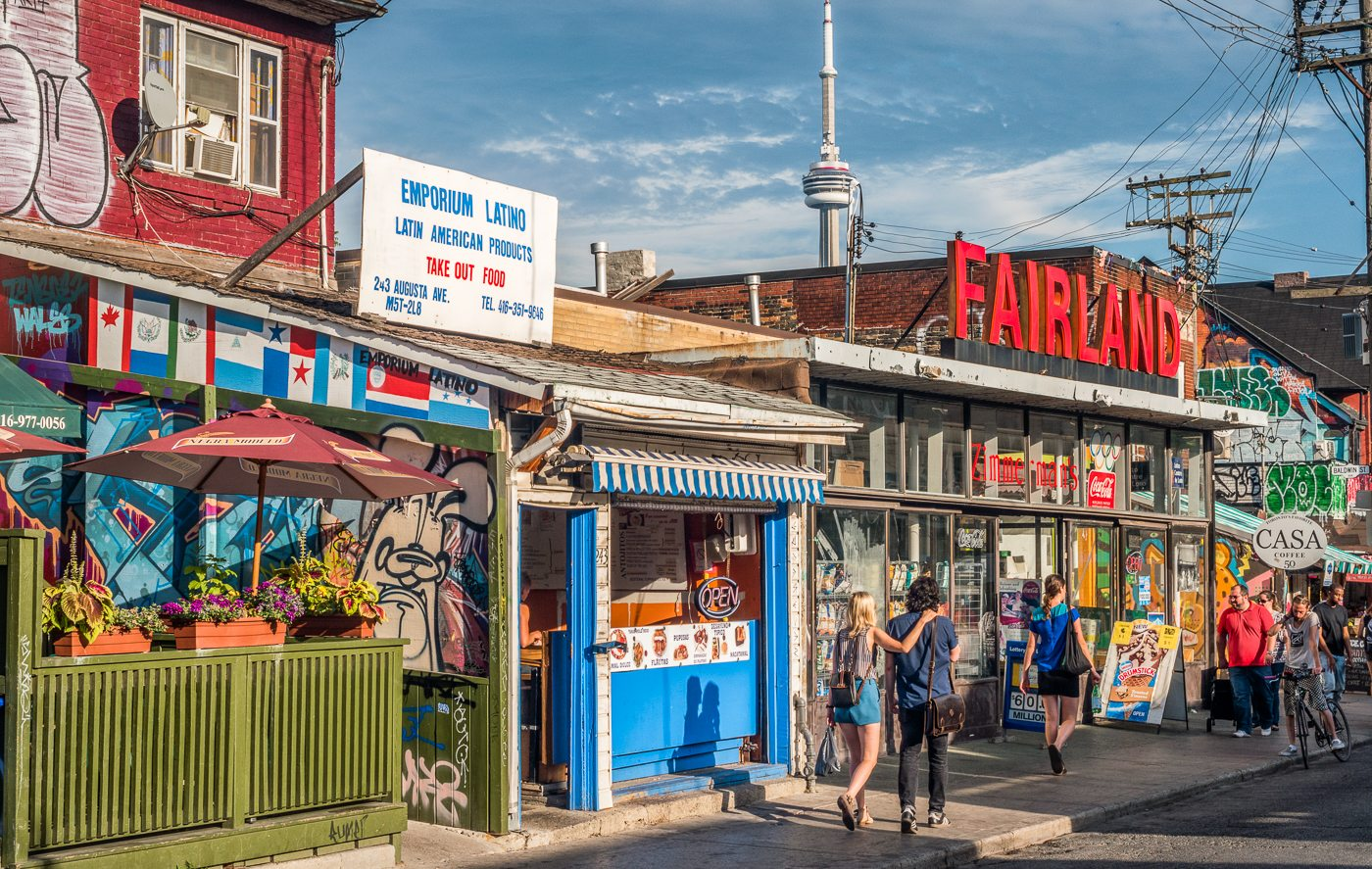Although living spaces in urban areas are usually smaller, they are often walking distance from vibrant street life, shops, and services, like in Kensington Market, pictured here. Photo by Ryan in the Torontoist Flickr Pool.