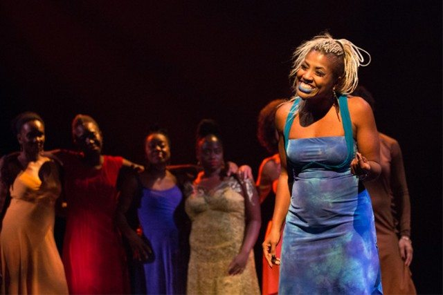 The Lady in Blue (SATE) speaks while the ensemble looks on. Photo by Cylla von Tiedemann.