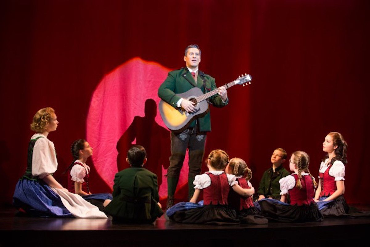 Baron Von Trapp (Nicholas Rodriguez) plays Edelweiss surrounded by his children in  The Sound Of Music.  Photo by Matthew Murphy.